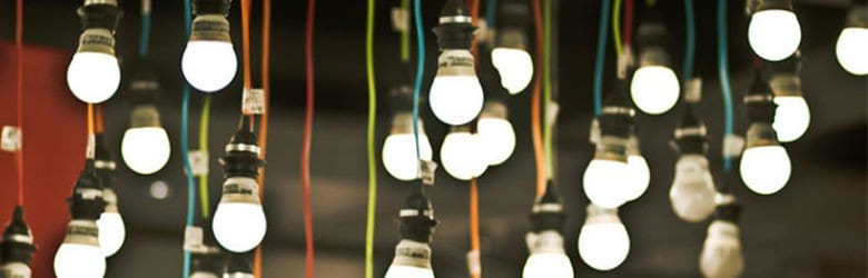 A photograph of many switched on hanging light bulbs.