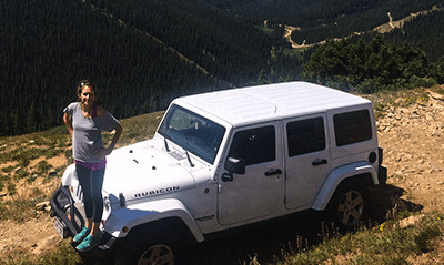 Mandy Mangold Wall with white Jeep Rubicon on mountain dirt road.