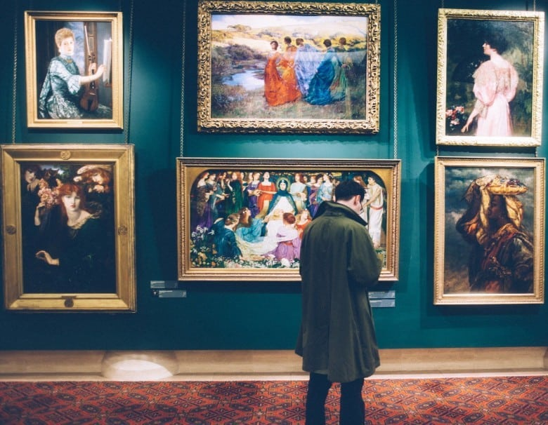 Man standing in front of a museum gallery wall - Photo by Clem Onojeghuo via Unsplash