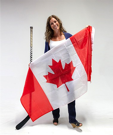 Christina Griggs holding a Canadian flag and a hockey stick.