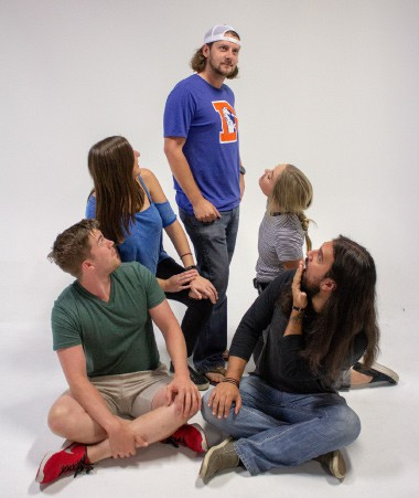 A photograph of four Inflow employees siting on the floor and looking up at a standing Shaun Elley.