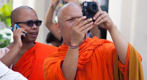 A photograph of two Buddhist monks. One is taking a photograph and the second is talking on a phone.