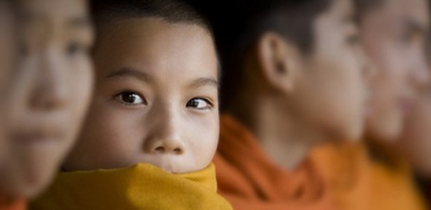 A photograph of a row of young Buddhists with one looking at the camera.