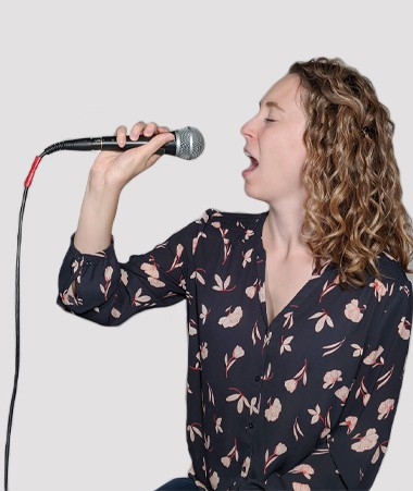 A photograph of Kate Miller singing into a microphone.