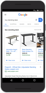 """A photograph of a smartphone displaying Google shopping ads for the search text """"buy standing desk."""" Ads are at the top of the search results. Each ad contains an image of the product and no text description."""