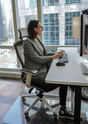 A photograph of MorganCodes sitting at a desk in an office using a glass chair mat.