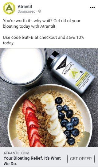 An Atrantil Facebook ad.  A short text advertises Atrantil as getting rid of bloat and offers a discount code. Below the text is a photograph of a bowl of granola topped with fruit, a glass of milk and a package of Atrantil.