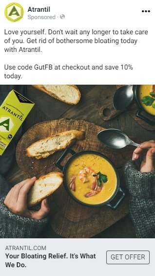 An Atrantil Facebook ad.  A short text advertises Atrantil as getting rid of bloat and offers a discount code. Below the text is a photograph of a person wearing a sweater and eating a bowl of yellow soup containing shrimp and toast served on a dark wood serving platter. A package of Atrantil is nearby.
