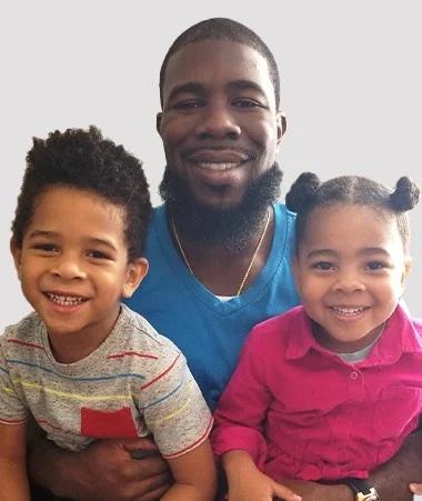 Calvin Carter holding two children.