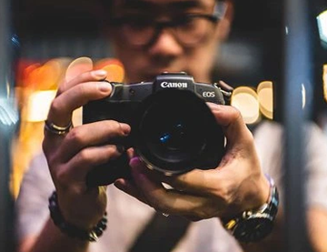 A photograph of a man holding a Canon camera in front of him.