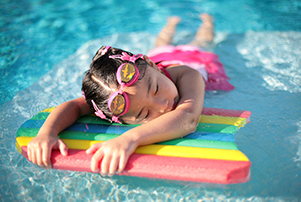 A photograph of a young girl resting her upper body on a float in a pool.