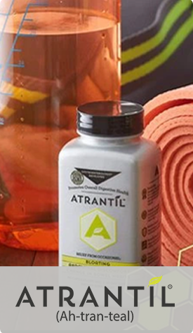 A photograph of an Atrantil bottle with a glass container with measurement lines and a yoga mat in the background. Logo: Atrantil (Ah-tran-teal).