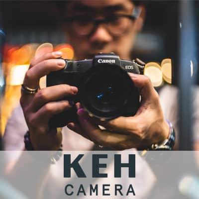 Logo: K E H Camera. A photograph of a man holding a camera.